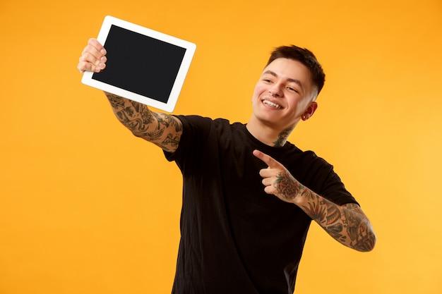 Retrato de um homem casual confiante, mostrando a tela em branco do laptop
