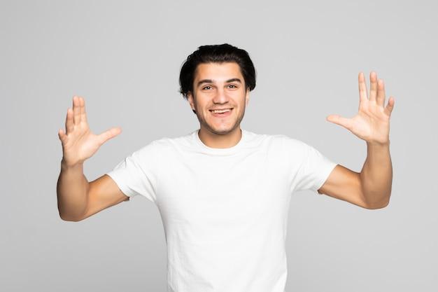Retrato de um homem casual e animado em pé com as mãos levantadas em branco