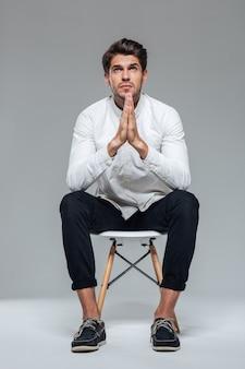 Retrato de um homem casual orando sentado em uma cadeira isolada em uma parede cinza