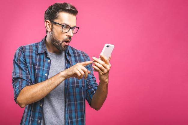 Retrato de um homem casual surpreso, olhando para o telefone móvel