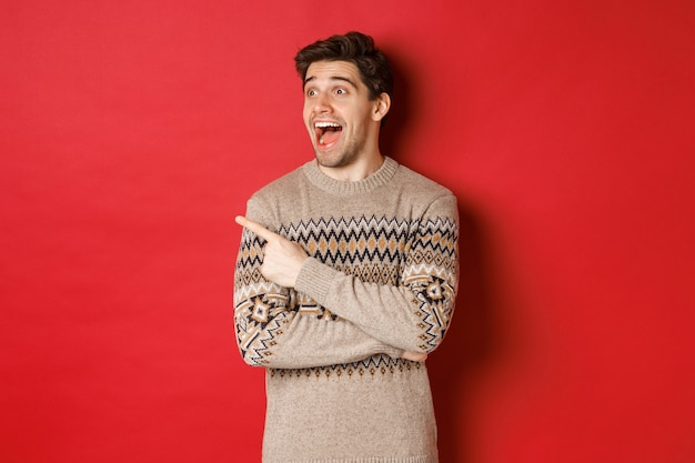 Retrato de um homem caucasiano atraente, comemorando o ano novo, férias de inverno, apontando o dedo e olhando para a esquerda com expressão de espanto, mostrando o anúncio de natal, em pé sobre fundo vermelho.