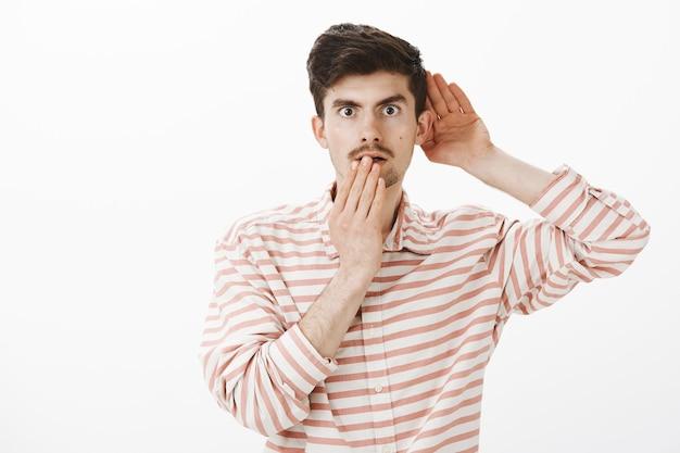 Retrato de um homem caucasiano atraente e intrigado, chocado, com uma camisa listrada da moda, segurando a mão perto da orelha e da boca, ouvindo uma conversa ou espionando, ouvindo algo chocante e interessante