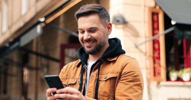 Retrato de um homem caucasiano com cabelo escuro por toda parte, nas ruas da cidade durante o dia, olhando para ...