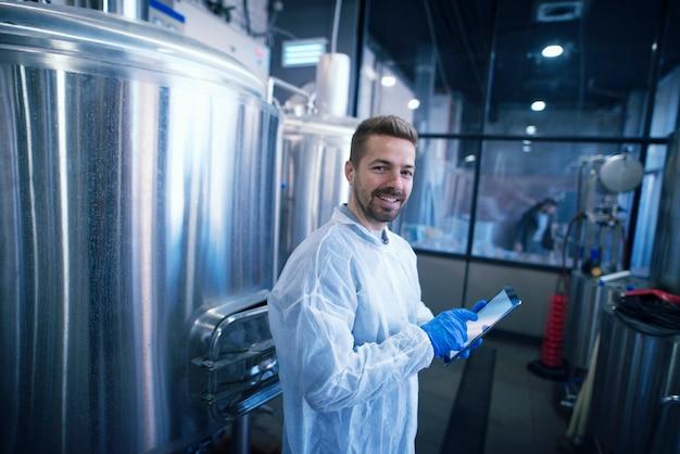 Retrato de um homem caucasiano em um terno branco parado perto dos reservatórios na planta de produção. trabalhador industrial com tablet