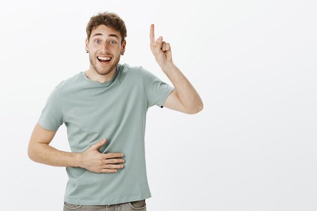 Retrato de um homem caucasiano simpático e bonito, com cabelos loiros e eriçados, levantando o dedo indicador e apontando para cima