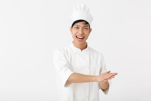 Retrato de um homem chinês feliz em uniforme de cozinheiro branco e chapéu de chef, sorrindo para a câmera em pé, isolado sobre uma parede branca