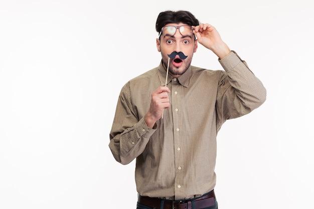 Retrato de um homem chocado segurando um pedaço de pau com bigode isolado em uma parede branca