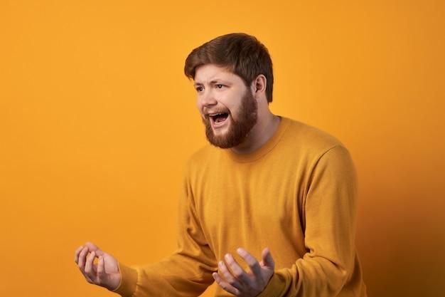 Retrato de um homem com a barba por fazer irritado e emotivo, cerrando os dentes e gesticulando com raiva enquanto discute com a esposa, irritou expressão facial negativa
