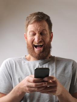 Retrato de um homem com barba entusiasmado com uma mensagem de texto