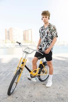 Retrato, de, um, homem, com, bicicleta amarela, escutar música