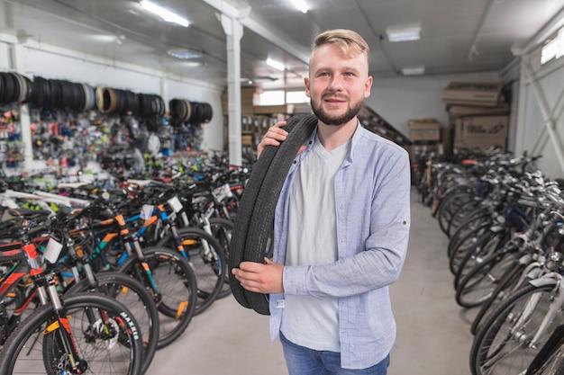 Retrato, de, um, homem, com, bicicleta, pneus, em, loja