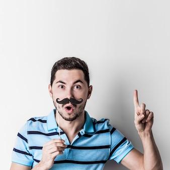 Retrato de um homem com bigode postiço dizendo algo importante com o dedo para cima