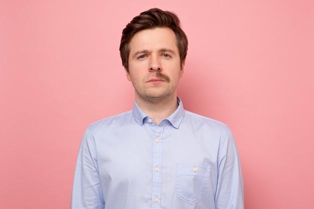 Retrato de um homem com meio bigode após fazer a barba em uma parede rosa