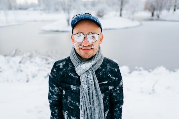 Retrato de um homem com neve no rosto ao ar livre, com rosto sorridente no dia de inverno nevado na natureza.