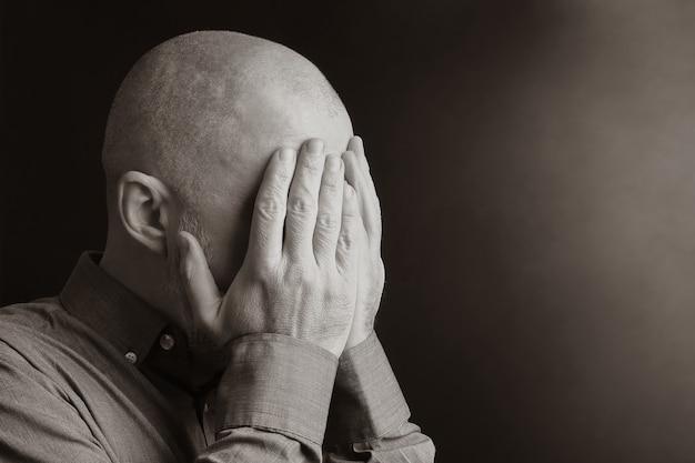 Retrato de um homem com o rosto de mãos fechadas. desespero e depressão. vergonha e culpa. tristeza e exílio