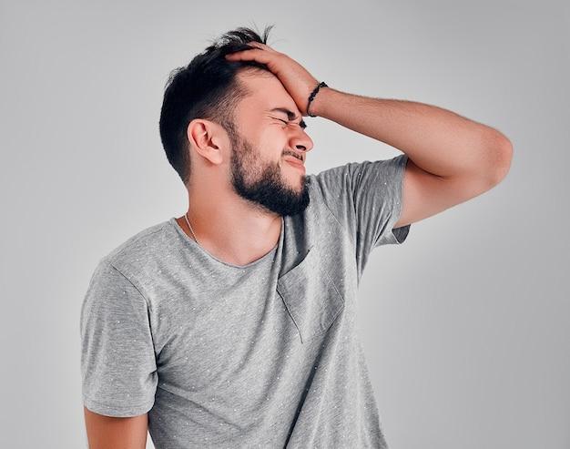 Retrato de um homem com o rosto fechado à mão. dor de cabeça. esqueci de algo