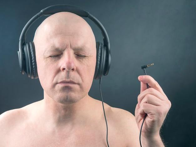 Retrato de um homem com os olhos fechados em fones de ouvido com um plugue na mão. busca de fonte de som