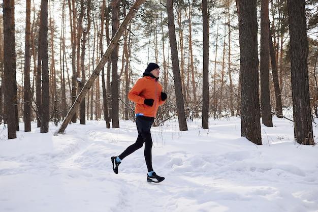 Retrato de um homem com roupas esportivas brilhantes, correndo por uma floresta de inverno. dia gelado