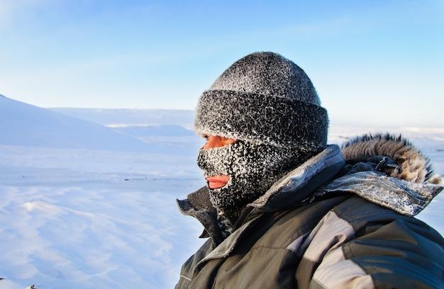 Retrato de um homem com um boné e uma máscara de esqui. inverno com geada.