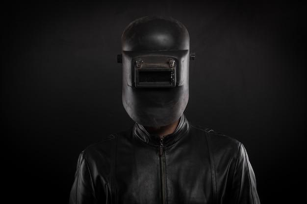 Retrato de um homem com um capacete de soldagem em um fundo preto