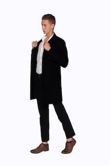 Retrato de um homem com um casaco preto e calças em um fundo branco