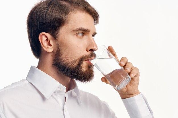 Retrato de um homem com um copo de água bebida refrigerando modelo de camisa leve.