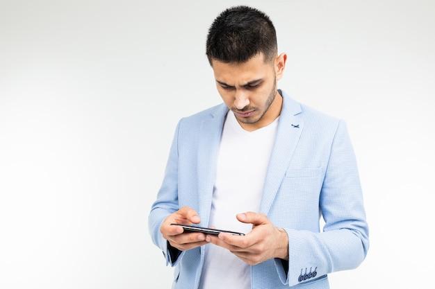 Retrato de um homem com um telefone nas mãos, jogando jogos em um fundo branco