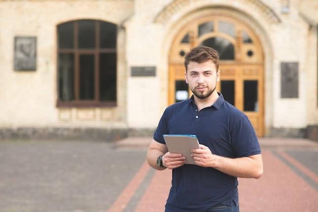 Retrato de um homem com uma barba em pé com um tablet nas mãos no contexto do edifício e olhando para a câmera.