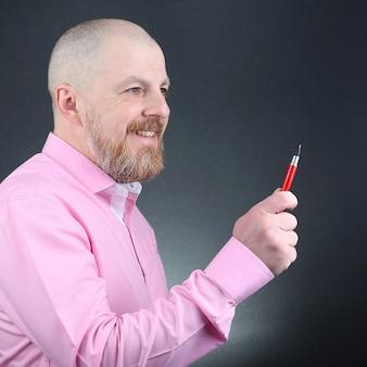 Retrato de um homem com uma camisa rosa e uma caneta vermelha na mão