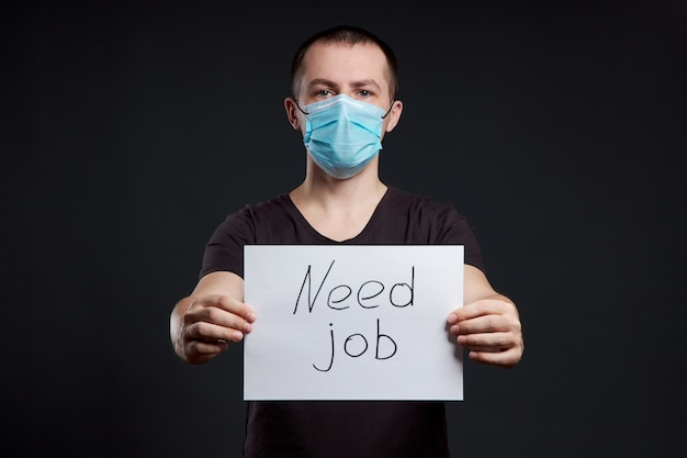 Retrato de um homem com uma máscara médica com um sinal de necessidade de trabalho no escuro