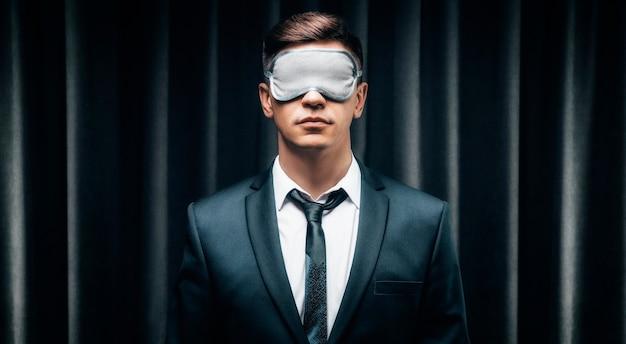 Retrato de um homem com uma máscara para dormir. ele está contra o pano de fundo de uma cortina
