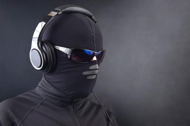 Retrato de um homem com uma máscara preta e óculos escuros ouvindo música em fones de ouvido