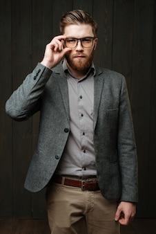 Retrato de um homem concentrado e casual, de óculos escuros, isolado no fundo preto de madeira.