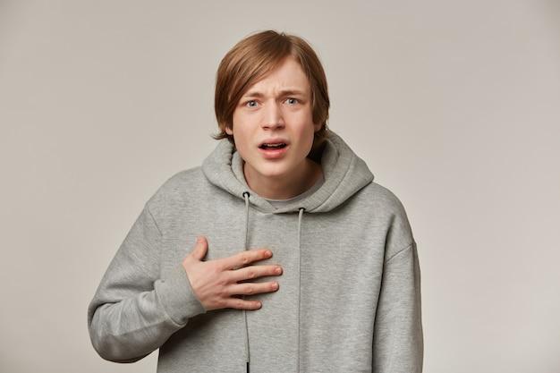 Retrato de um homem confuso e desnorteado com cabelo loiro. usando um capuz cinza. conceito de pessoas e emoção. apontando para si mesmo com incerteza.