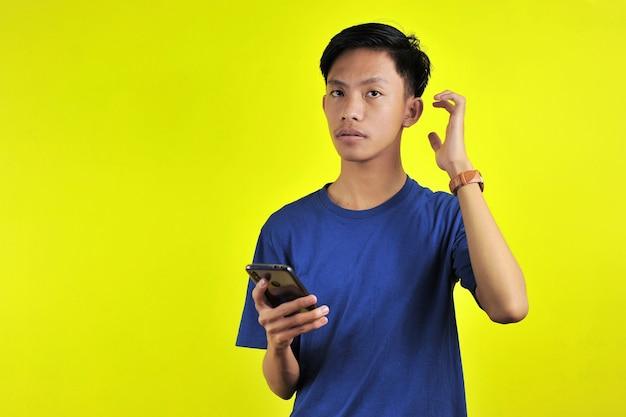 Retrato de um homem confuso olhando para um smartphone, isolado em um fundo amarelo