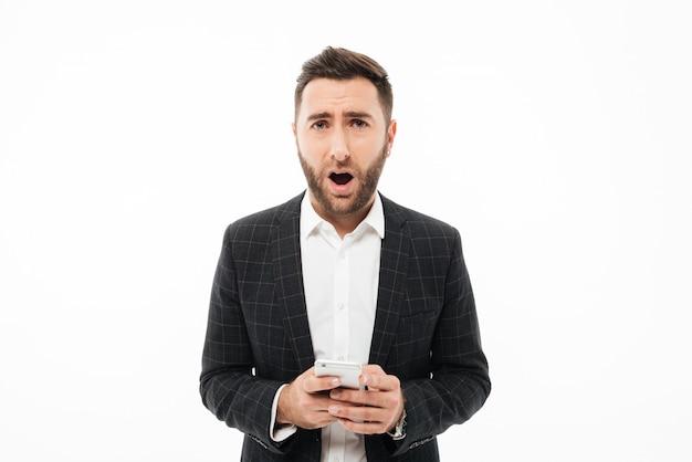 Retrato de um homem confuso, segurando o telefone móvel