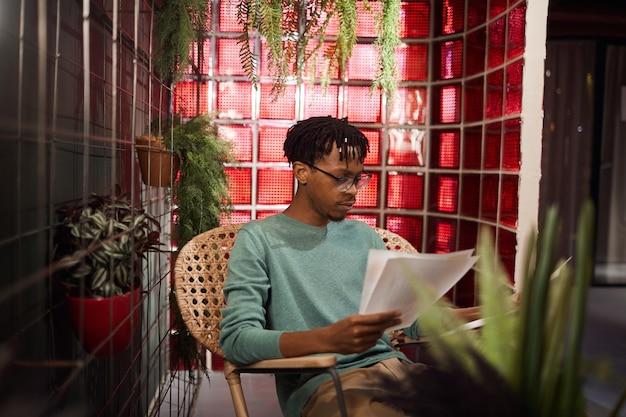 Retrato de um homem contemporâneo africano trabalhando com documentos enquanto está sentado em um café decorado com plantas