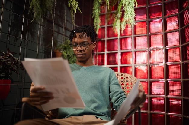 Retrato de um homem contemporâneo africano trabalhando com documentos enquanto está sentado no salão do café