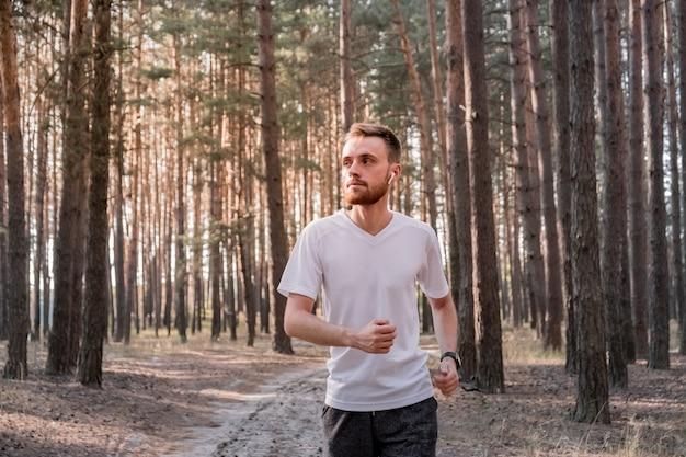 Retrato de um homem correndo pela floresta de pinheiros em um dia ensolarado