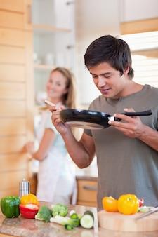 Retrato de um homem cozinhando enquanto seu noivo está lavando a louça