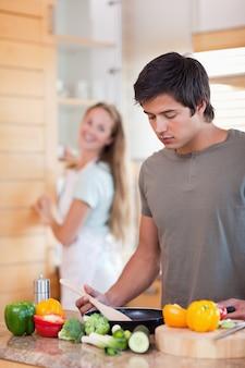 Retrato de um homem cozinhar enquanto sua esposa está lavando a louça