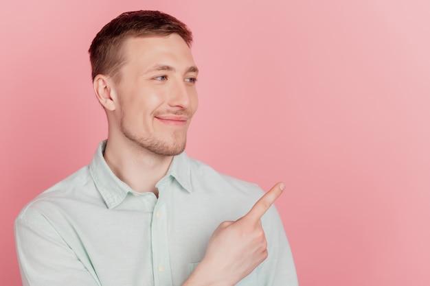 Retrato de um homem curioso positivo indica o espaço vazio do dedo olhando de lado no fundo rosa