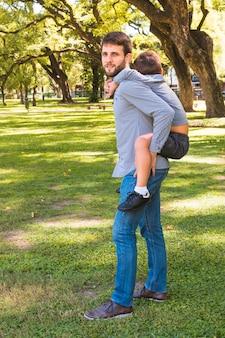Retrato, de, um, homem, dar, carona piggyback, parque