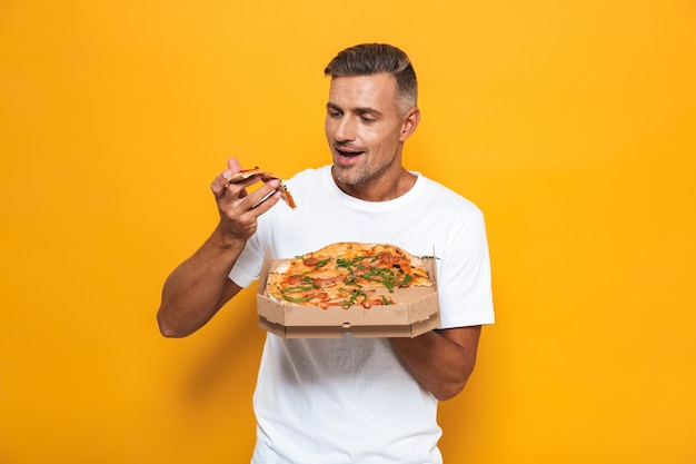 Retrato de um homem de 30 anos com a barba por fazer, com uma camiseta branca, segurando e comendo pizza em pé, isolado no amarelo