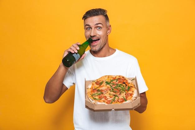 Retrato de um homem de 30 anos com a barba por fazer, vestindo uma camiseta branca, bebendo cerveja e comendo pizza em pé, isolado no amarelo