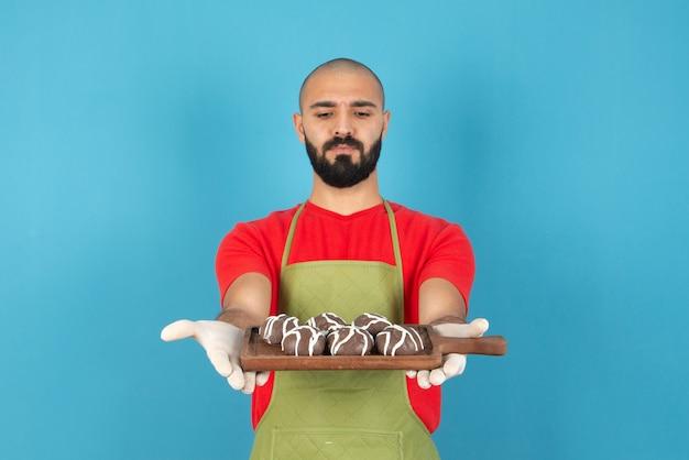 Retrato de um homem de avental segurando uma placa de madeira com biscoitos revestidos de chocolate.