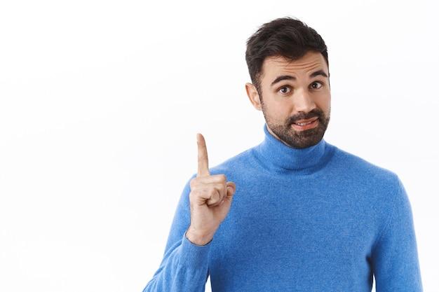 Retrato de um homem de barba inteligente e bonito adiciona solução, tem uma ideia ou sugestão, levantando um dedo para dizer uma recomendação, dar conselhos como ficar de pé sobre uma parede branca