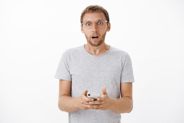 Retrato de um homem de barba maduro chocado preocupado, abrindo a boca chocado segurando um smartphone olhando para ler uma mensagem estranha e perturbadora posando