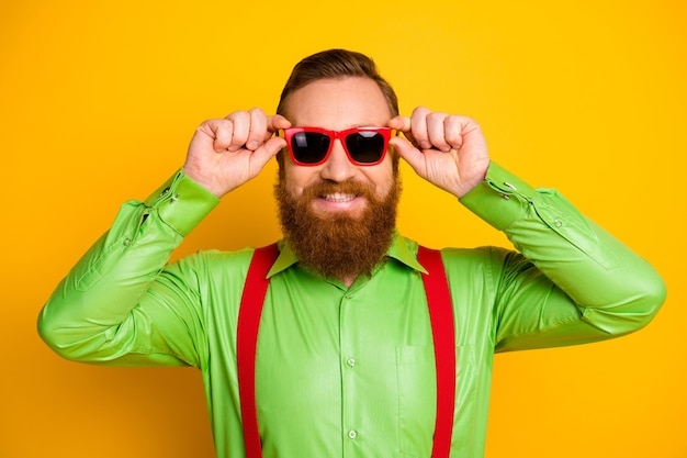 Retrato de um homem de barba vermelho imponente e amigável, curtindo as férias da primavera, toque em especificações modernas, use roupas bonitas isoladas sobre cores vibrantes