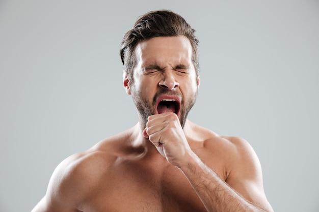 Retrato de um homem de beraded entediado com ombros nus bocejando
